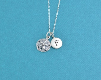 Little girl's sand dollar necklace in sterling silver on a sterling silver cable chain and personalized with sterling silver initial charm.