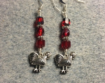 Silver chicken charm dangle earrings adorned with dark red Czech glass beads.
