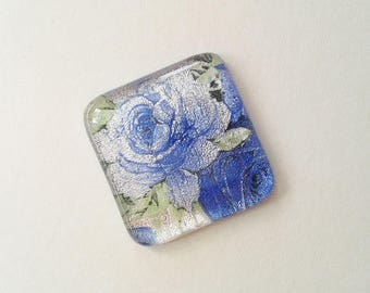 Dichroic rose cabochon, made from silver dichroic glass with blue floral rose pattern.