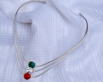 metal collar choker necklace with sparkling red, green, and white rhinestones.
