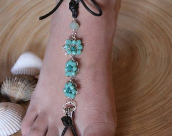 Bare sandals with flowers of green crystals