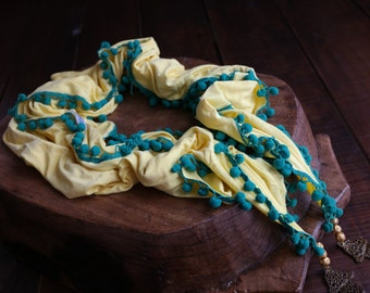Yellow scarf with green pom poms and 'the hand' medallions