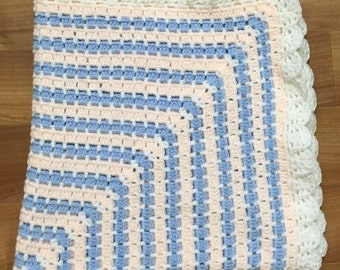 Crocheted pale blue and peach baby blanket