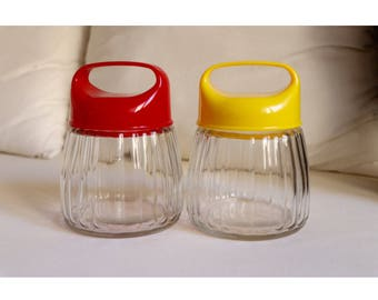 2 glass containers from the 50's vintage red and yellow tops from plastic