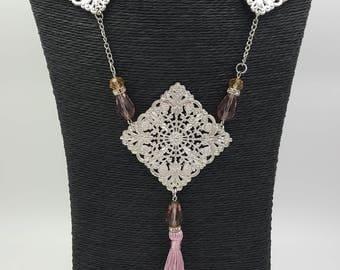 Collier filigrane mi-long lilas et argenté avec pompon.