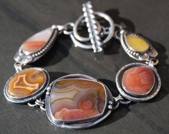 laguna lace agate, agua nueva agate, amber, and sterling silver metalwork link bracelet