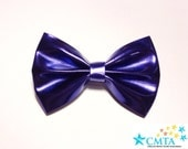 One purplish blue faux leather hair bow. Portion of sale goes to charity. Cruelty-free.