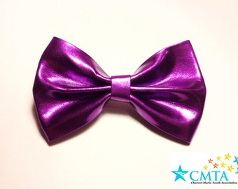 One magenta purple faux leather hair bow. Portion of sale goes to charity. Cruelty-free.