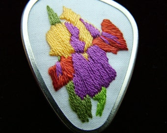 Hand embroidered jewellery brooch pin. Silver colour brooch with embroidered Iris design.