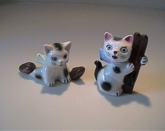 Two vintage 1950's ceramic black and white ski cat and ice skating cat