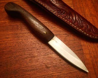 Hand carved black walnut patch knife with ornate tooled leather sheath.