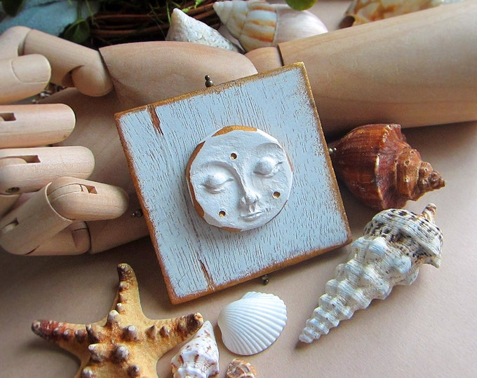"""Moon Goddess wall hanging. Hand sculpted clay moon on a wooden blank. Decorated with white & gold paint. Size 3"""" x 3"""". Comes with a hanger."""