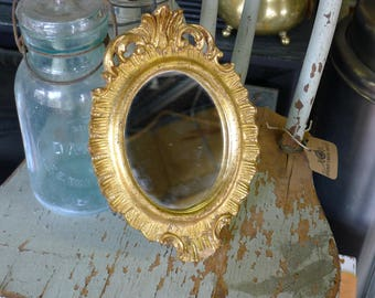 Oval accent mirror in gold plaster frame