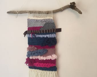 Woven wall hanging on driftwood in fuchsia and teal