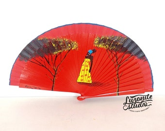 Fan red with an African woman and silhouettes of trees hand painted, hand-painted Spanish fan