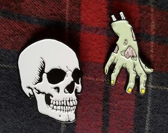 "Pin / badge: ""Zombie's hand"" gold ""Skull"" (zombie hand and skull)"