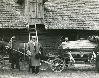 Old 1930s post mortem photo, funeral procession with horse-drawn hearse in European village, mourning photo, cemetery, old antique snapshot