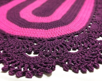 Crocheted oval purple rug with beautiful details.