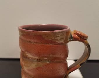 Handmade gold and orange mug, with red interior