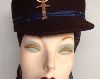 Brown Pillbox Cap Trimmed with a Sun Worshipping Figurine and Blue Cord