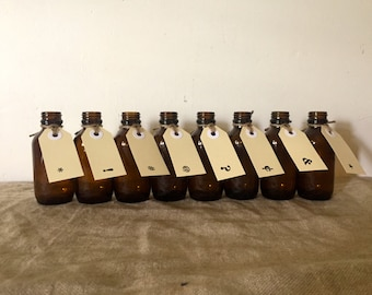 Eight amber apothecary bottles, each with a luggage tag. Great typo graphics. Vintage / Industrial decor.