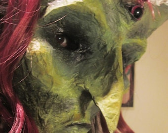 Mask from paper mache. Witch redhead green with third eye.