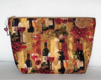 Wine cosmetic, makeup bag, small cosmetic pouch with a wine theme fabric and complementary wine glass zipper closure.