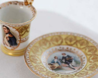 "Pale yellow and goldcolor Empirestyle demitasse, ft. Napoléon Bonaparte and a ""scene galante""; goldcolor décor and handle."