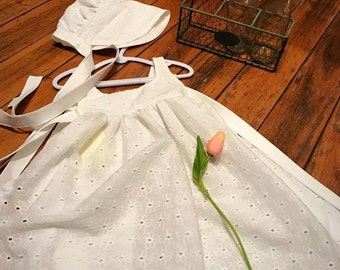 A sweet white eyelet pinny, with matching bonnet.