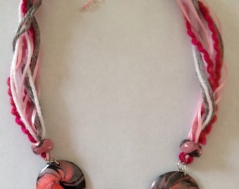 Three-medallion necklace in pink and black swirl pattern.