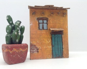 256 - Santa-Fe style adobe house with a wood roof, plaster wall with exposed brick.