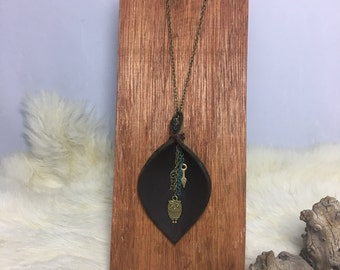 Necklace with a folded leather piece with charms