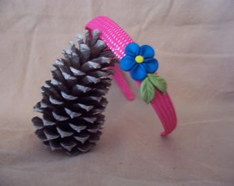 Pink headband with pretty blue flower and leaves.
