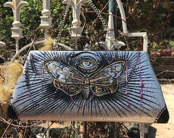 Metallic evening handbag with hand painted moth and eye.