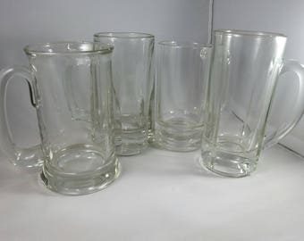 Set of four 4 unique clear glass beer steins.