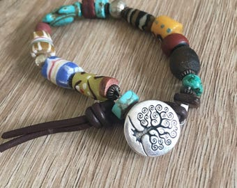 Multi coloured Boho-chic bracelet handmade with trade beads. For festivals and summer wear. Fastens with Tree of Life button.