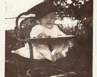 Original Vintage Photograph Snapshot Baby Wearing Big Cap in High Chair Outdoors 1910s-20s