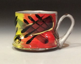 Red yellow black and gold mug