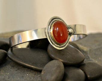 Carnelian cuff bracelet with 14K gold bezel.  Solid heavy sterling silver.