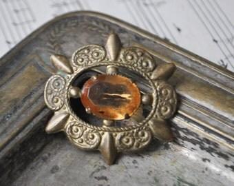 Vintage brass brooch with glass rhinestone.