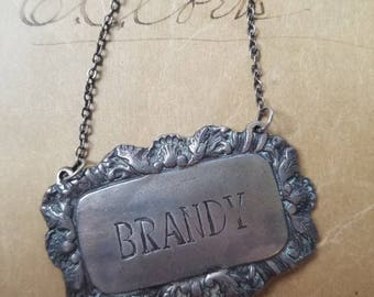 fancy a drink - pewter brandy liqour bottle tag label, vintage antique barware, ornate design, neat piece for assemblage