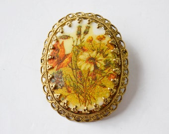Vintage 80 year brooch with metal filigree and plastic center