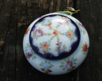 Porcelain round box with hand painting. Small vintage unmarked porcelain box with multicolored flowers and blue edge with gold accents.