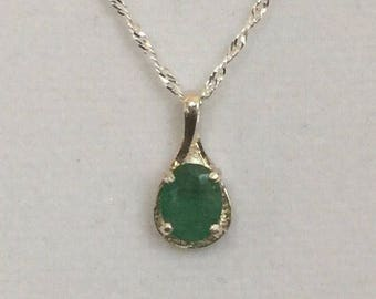 Emerald pendant set in fancy sterling oval setting upon a sterling silver chain.