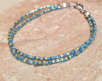Blue and gold seed bead bracelet made with Miyuki seed beads, Hill Tribe silver faceted and rondelle beads with a silver trigger clasp