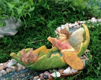 Miniature Boy Fairy in a Leaf Canoe with a Bunny