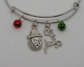 Christmas themed silver charm bracelet. One red and one green jingle bell that really jingle, Santa and a reindeer.
