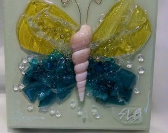 Yellow and aqua glass butterfly on green