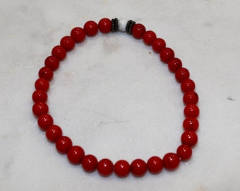 Beaded red bracelet with black accent bead