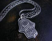 Deep etched hamsa pendant with evil eye, stars and moons.